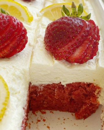 Strawberry Lemonade Cake starts with a lemon cake mix + strawberry pie filling! So easy to make, crazy moist, and topped with the fluffiest & lightest whipped pudding frosting.