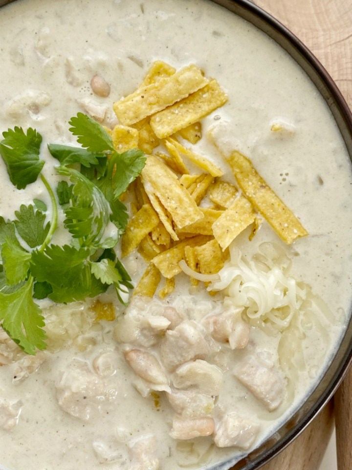 White Chicken Chili is a creamy white chili that's made in just one pot! Chunks of chicken and white beans in a chicken broth green chili base and sour cream and heavy cream to make it super creamy.
