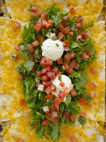 Mexican Lasagna is layered with flour tortillas, cheese, and a creamy chicken mixture of black beans, corn, sour cream, salsa verde, and seasonings. An easy, one pan dinner that is best served with all the toppings. We love lettuce, pico de gallo, and sour cream!