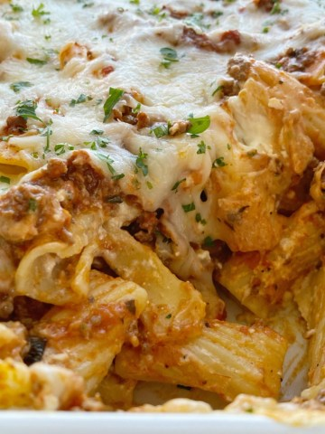 Close up shot of cheesy and creamy lasagna casserole with rigatoni pasta noodles.