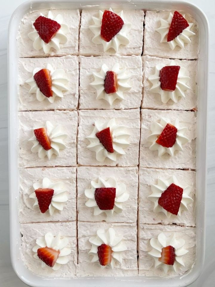 Strawberry cake recipe topped with fluffy frosting and strawberries.