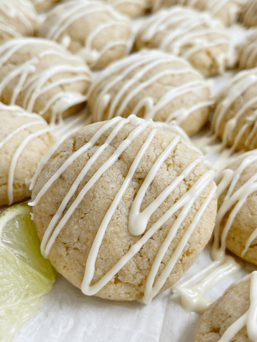 Cookies with key lime juice on a cookie sheet with a lime wedge next to it.