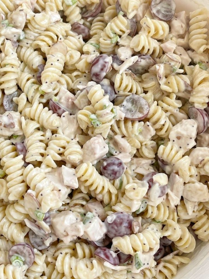 A bowl of pasta salad with chicken, grapes, poppy seeds, and almonds.
