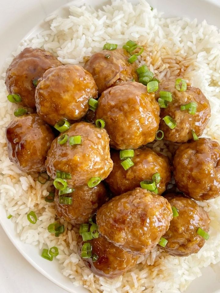 Overhead picture of turkey meatballs on top of rice on a white plate.
