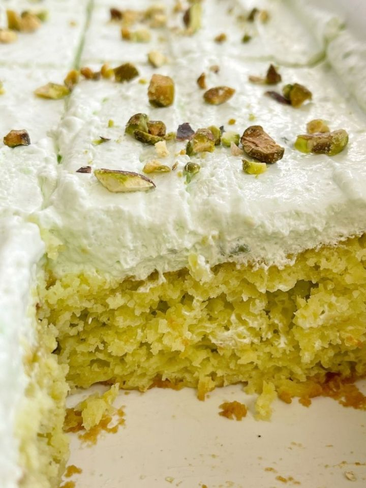 Cake inside a white pan topped with frosting and pistachios.