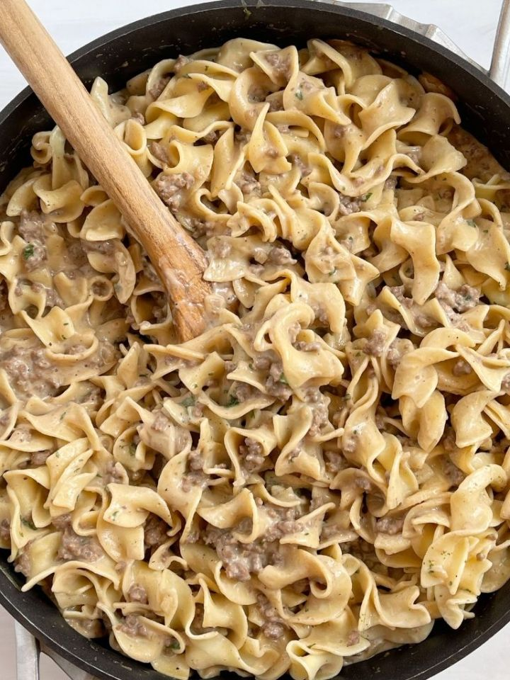 A skillet pan with beef stroganoff and a wooden spoon in it.