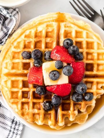 Hero shot of a stack of waffles topped with syrup, butter, and fruit.