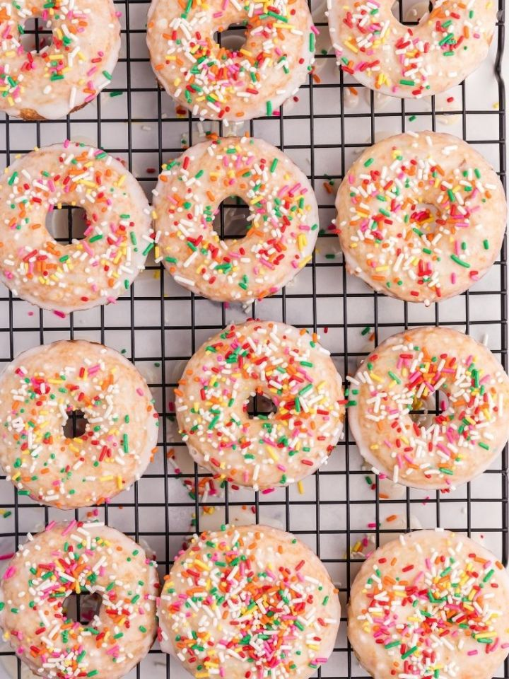 A cooling rack with donuts with a glaze and sprinkles.