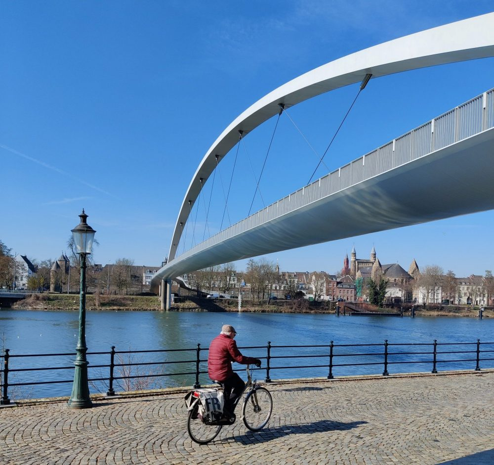 A bridge in Maastricht with a cyclist and old street light