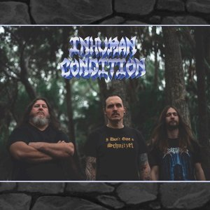 Members of Inhuman Condition stand in the woods.