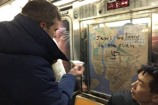Graffiti being cleaned off subway car