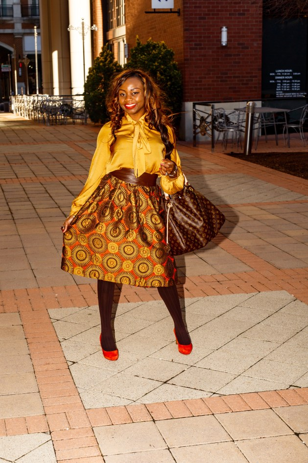 Gold and orange print midi circle skirt with gold tie neck blouse