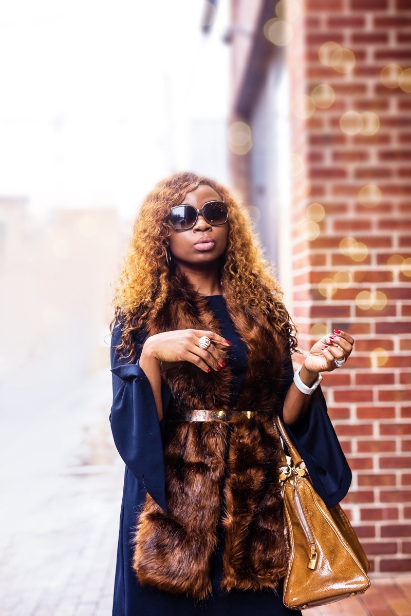 woman wearing gucci sunglasses and faux fur stole