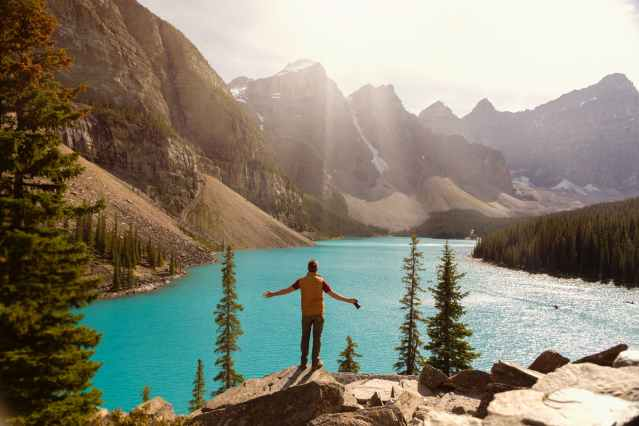 a man standing on the cliff over a lake