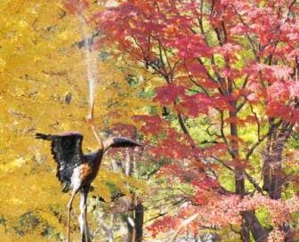red maple leaves and yellow maidenhair leaves and a crane sculpture
