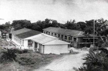 当時村における唯一の医療機関としてまさしく村民の命の綱でした。 現在の町立図書館のある敷地に建っていました。右奥の建物(工事中)は伝染病棟です。