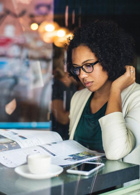 Black woman reading newspaper - 480x669