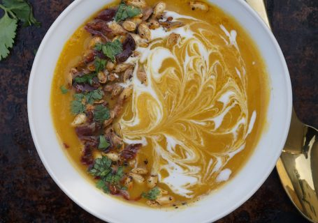 Bowl of Creamy Butternut Squash soup garnished with a swirl of coconut cream, beef bacon bits, and pepitas