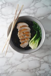 A grey bowl with chopsticks, broth, black noodles, bok choy, and chicken for a Asian Chicken noodle soup bowl