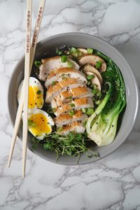 A grey bowl with chopsticks, broth, black noodles, bok choy, chicken, egg,s and greens for a Asian Chicken noodle soup bowl