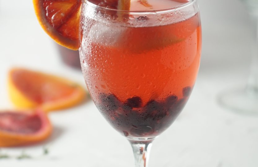 Glass with pink wine and a slice of blood orange on the glass. Faded slices of blood orange, a glass and a pitcher in the backgorund