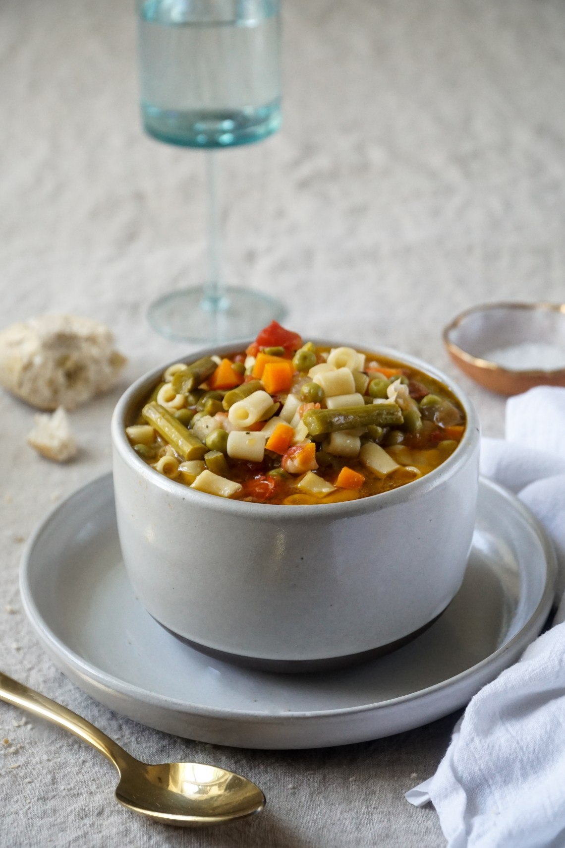 A bowl of This light spring minestrone soup on a plate with bread, water glass, and salt dish in the background.