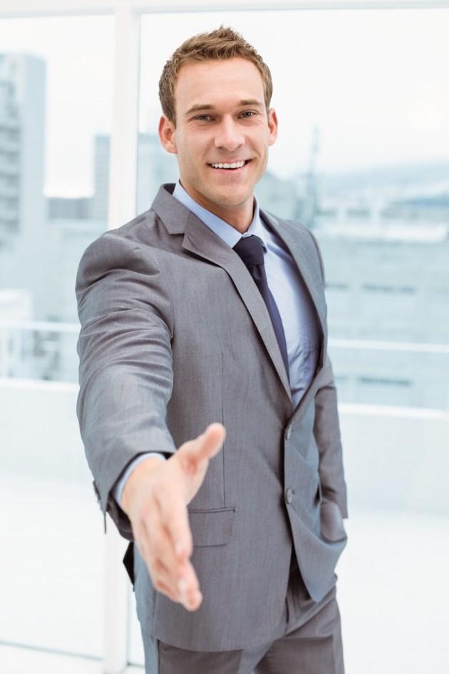 Portrait of smart businessman offering handshake