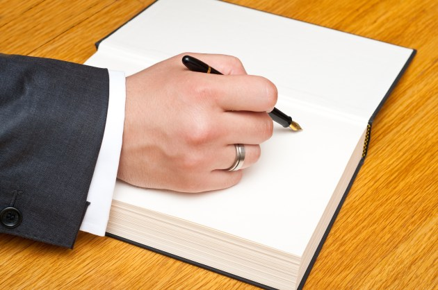 man signing first blank page of a book