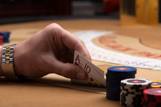 Player in casino holding in hand cards sitting at table selective focus