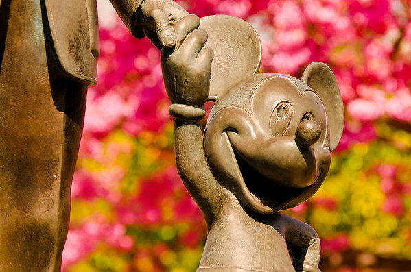Mickey Mouse holding hands with Walt Disney on Partners at Disneyland.