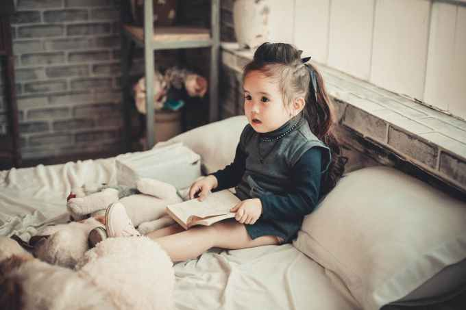 toddler girl wearing long sleeved top reading book while sitting on bed