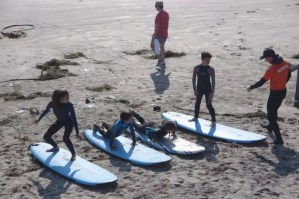 learning to stand up on a surfboard during lesson