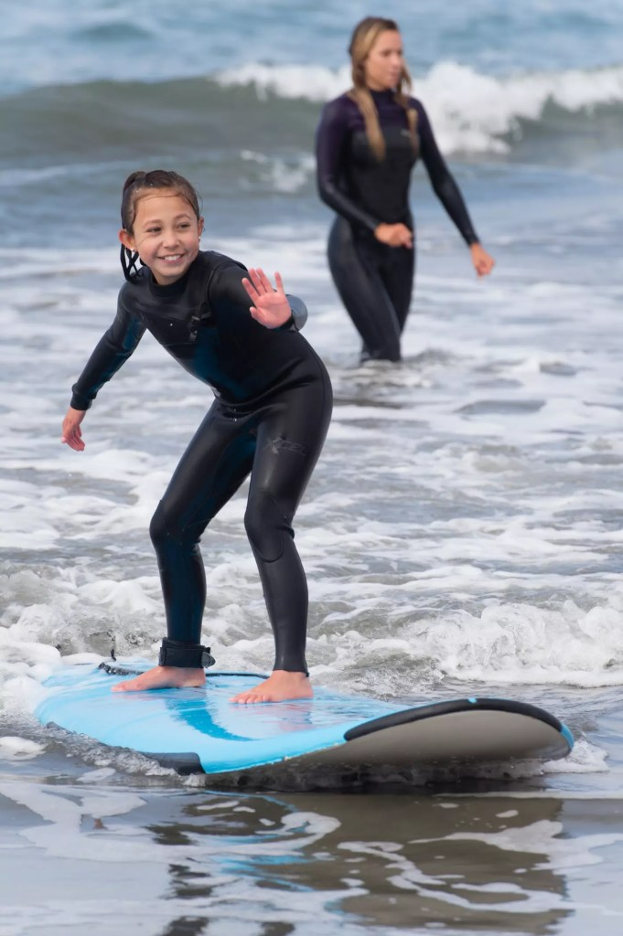 young girl surfing waves