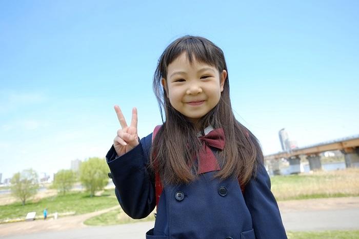 女の子の笑顔とピースサインのイメージ画像