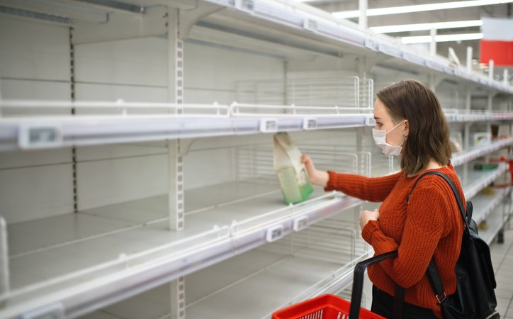Young woman standing in front of empty shelf in a supermarket