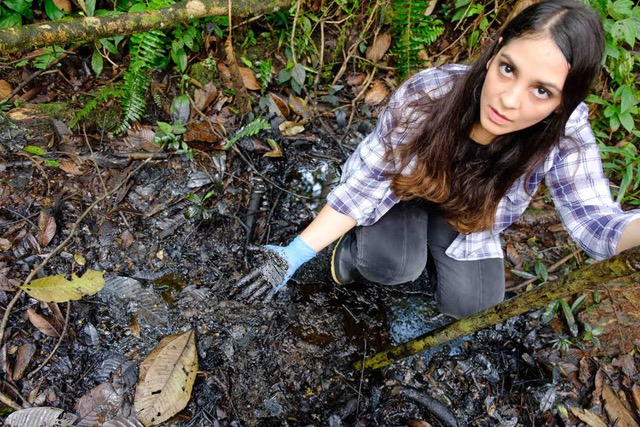 Maria Cecilia Herrera shows the oil pollution left behind by Chevron-Texaco in Ecuador, which has led to an epidemic of cancer and birth defects. (Enrique Aviles, Ecuador Amazon Restoration Project)