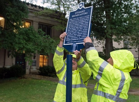 Penn State Office of Physical Plant employees Vince Benner, left, and Jim Simpson erected a new Penn State Historical Marker commemorating college radio at Penn State as a pioneer in the field that continues to broadcast and teach today.