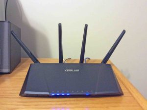Picture of the Asus RT-AC87R gigabit router, front view, installed and operating on office desk.