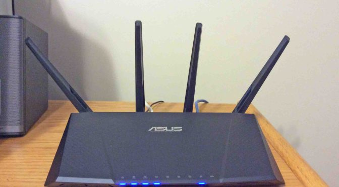 Picture of the Asus RT-AC87R Wireless Router, Front View, Installed and Operating on office desk.