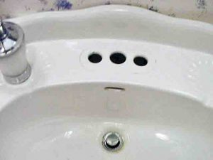 Picture of our bathroom sink with broken faucet removed and the holes cleaned out.
