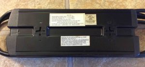 Bottom view image of the Belkin Isolator F5C980-TEL surge protector. Showing labels and cable keeper.
