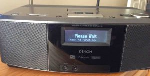 """Picture of the Denon S-32 Internet Radio, Displaying the, """"Please Wait, Checking Function,"""" message, just after turn-on."""