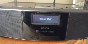 Picture of the Denon S-32 Internet Radio, displaying the blinking -Please Wait- message.
