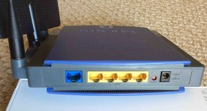 Picture of the back view of the Linksys WRT300N WiFi router. Rear view. Showing the antennas (left), wide area and local Ethernet ports, reset button, and power port.