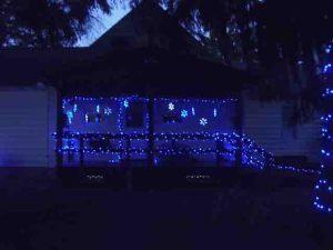Picture of our LED Christmas light decorations outdoors, house south porch, showing lighted snowflakes, and small LED strings on porch railings and banisters.