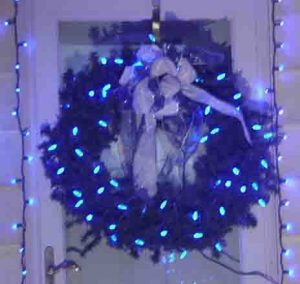 Outdoor Christmas light decorating ideas pictures. Picture of our LED Christmas lights outdoors, on decorated wreath hanging on west door at this home.