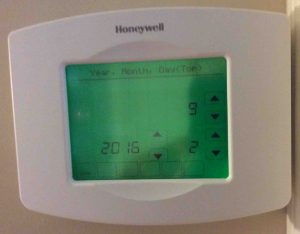 Picture of the Honeywell RTH8580WF Thermostat, prompting for current date and time.