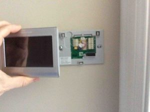 Picture of the Honeywell RTH9580WF Internet Thermostat, being snapped onto wall plate.