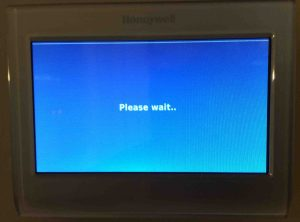 Picture of the Honeywell RTH9580WF smart thermostat, showing the Please Wait screen after reset.