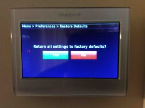 Picture of the Honeywell RTH9580WF smart thermostat, showing the Restore Factory Defaults confirmation screen.
